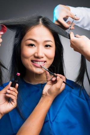 Photo pour Beaucoup de mains maquiller et cheveux de coupe de la jeune femme vietnamienne - image libre de droit