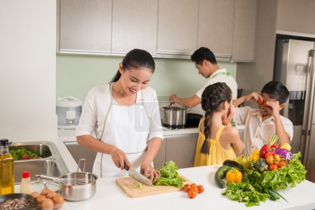 Photo for Parents cooking, while their children playing in the kitchen - Royalty Free Image