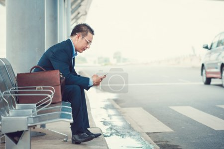 Photo for Elegant businessman texting while sitting at the bus stop in the airport - Royalty Free Image