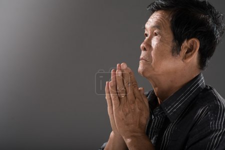 Senior Vietnamese man praying
