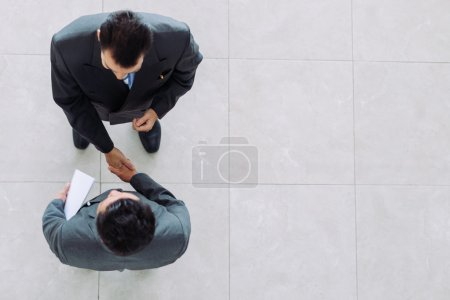 Photo for Business partners shaking hands as a symbol of unity, view from the top - Royalty Free Image