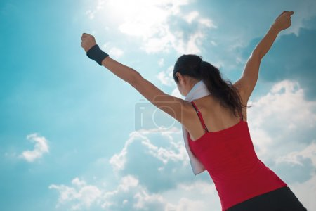 Photo for Active woman with outstretched arms against the blue sky, rear view - Royalty Free Image