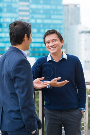 Photo for Asian business people chatting outdoors during the break - Royalty Free Image