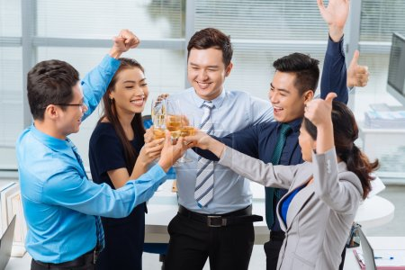 Successful business team clinking glasses