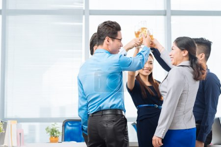 Business team raising glasses