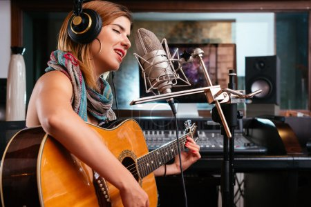 Photo for Young woman with guitar recording a song in the studio - Royalty Free Image