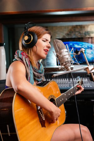 Photo pour Retrato de uma linda mulher tocando guitarra e cantando uma canção - image libre de droit