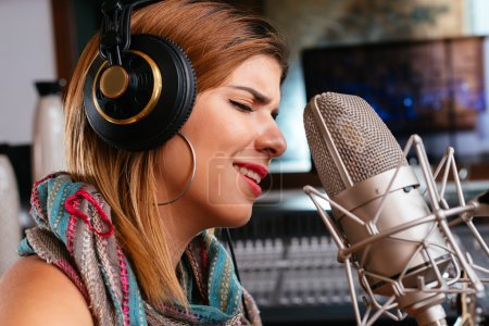 Photo for Close-up portrait of beautiful woman in headphones singing - Royalty Free Image