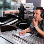 Hispanic sound engineer working at mixing panel in...