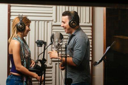 Photo pour Chanteurs en riant tout en enregistrant une chanson en studio - image libre de droit