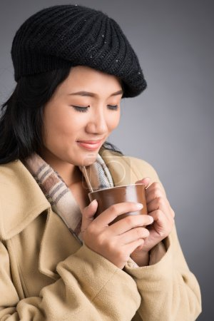 Woman in coat enjoying hot drink