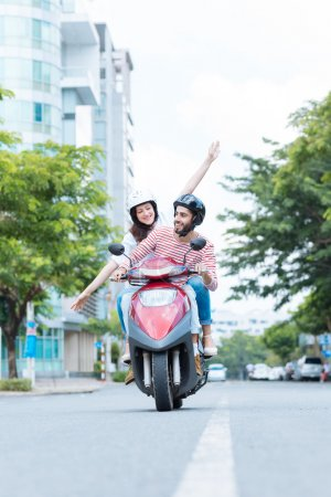 Photo for Happy excited couple riding a motor scooter, the body of the scooter has been changed digitally - Royalty Free Image
