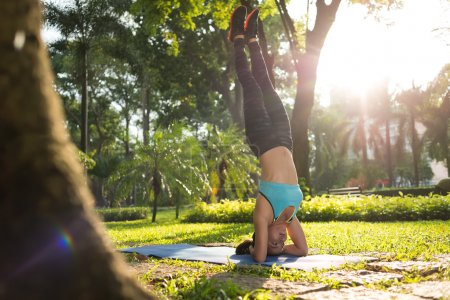 Photo for Woman performing elbow stand on yoga mat in park - Royalty Free Image