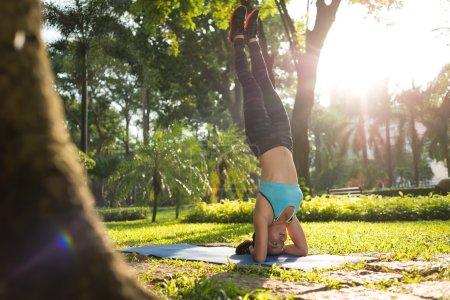 Photo pour Woman performing elbow stand on yoga mat in park - image libre de droit