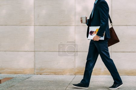 Cropped image of businessman with coffee and magaz...