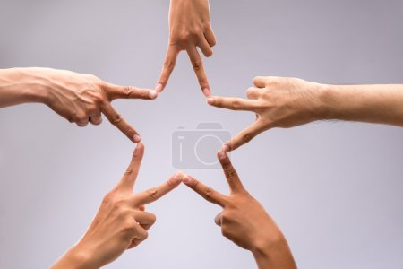 Photo for People forming star shape with their fingers - Royalty Free Image