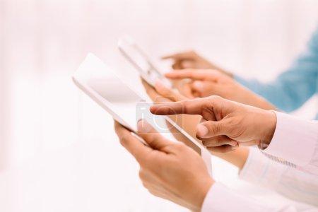 Photo pour Les mains des hommes d'affaires utilisant des tablettes numériques, se concentrer sur l'avant-plan - image libre de droit