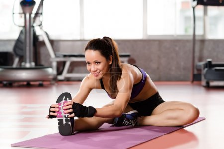 Photo for Woman stretching legs in sports club - Royalty Free Image
