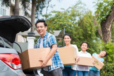 Familia poniendo cajas de cartón en el coche