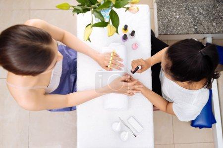 Woman receiving manicure