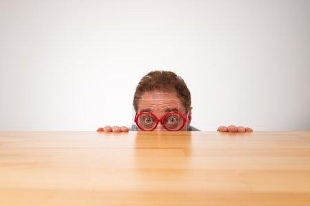Photo pour Mature homme dans des lunettes jetant un coup d'oeil sur la table - image libre de droit