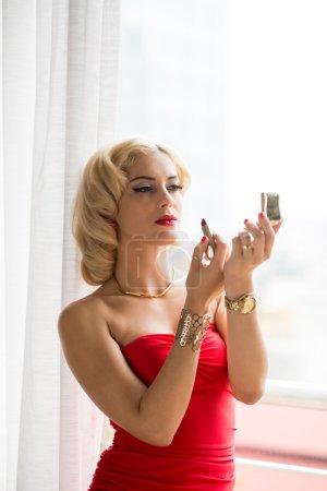Blond Applying lipstick