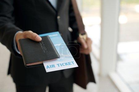 Photo pour Gros plan d'un homme d'affaires qui donne son passeport et son billet à l'aéroport - image libre de droit