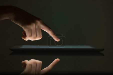 Photo pour Écran tactile doigt de tablette numérique sur fond noir - image libre de droit