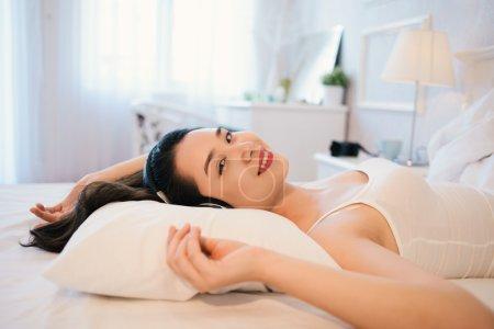Photo pour Jeune femme souriante dans un casque relaxant au lit - image libre de droit