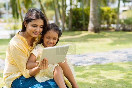 Photo for Indian mother and daughter sitting in the park and using digital tablet together - Royalty Free Image