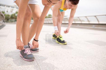Joggers tying shoelaces