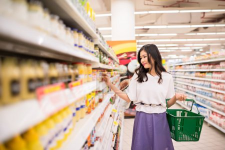 Photo for Lovely young woman shopping at the supermarket - Royalty Free Image