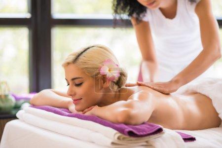 Photo pour Belle jeune femme appréciant le massage de dos dans le salon - image libre de droit