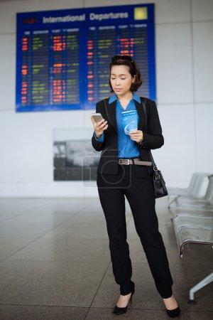 Photo pour Portrait complet d'une femme d'affaires avec carte d'embarquement lisant un message - image libre de droit