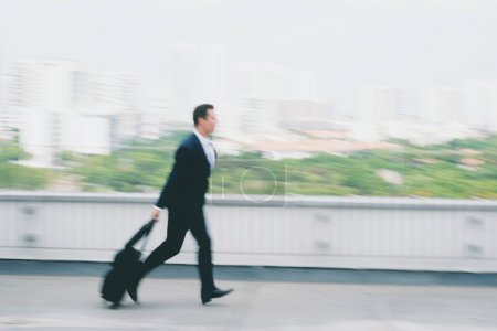 Businessman with a suitcase running