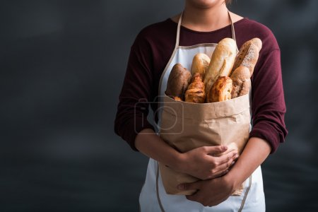 Photo for Cropped image of woman holding grocery bag full of fresh bread - Royalty Free Image