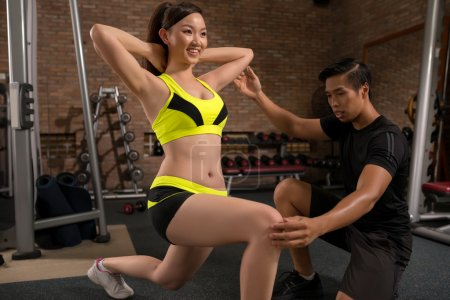 woman training in gym with instructor