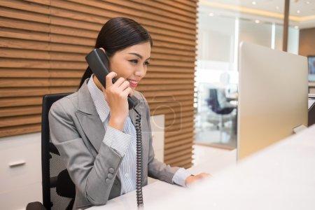 Photo pour Jolie réceptionniste vietnamienne parlant au téléphone sur son lieu de travail - image libre de droit