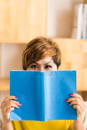 woman hiding behind a book