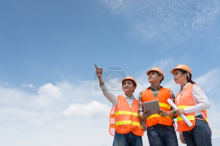 Photo for Team of architects looking at the building at the construction site - Royalty Free Image