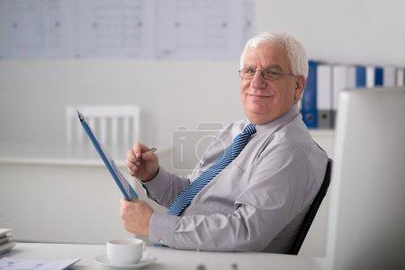 Photo pour Homme d'affaires senior souriant travaillant avec un document financier - image libre de droit