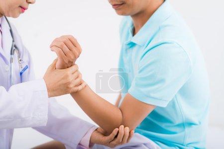 Orthopedist  examining injured arm