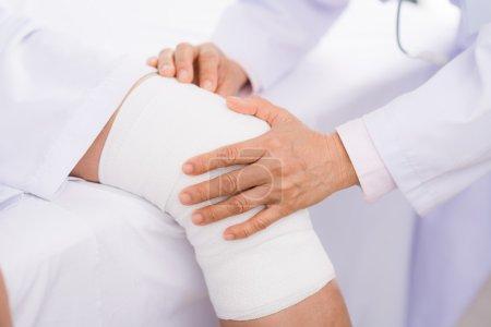 Orthopedist examining twisted knee