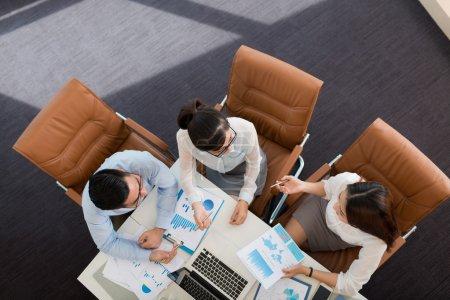 Foto de Compañeros de negocios asiáticos discutiendo informes financieros, vista desde arriba - Imagen libre de derechos