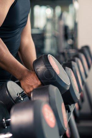 sportsman choosing dumbbells in the gym