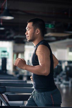 Vietnamese man running on the treadmill