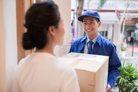 Photo for Cheerful Asian postman giving cardboard box to the woman - Royalty Free Image