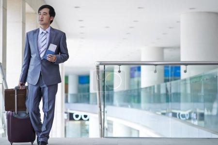 Photo pour Entrepreneur asiatique marchant avec des bagages à l'aéroport - image libre de droit