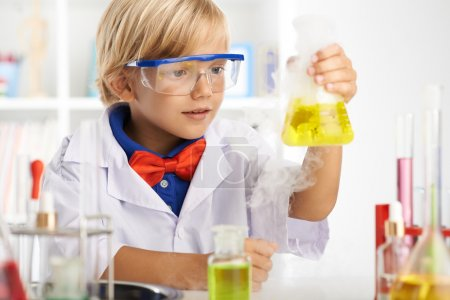 Photo for Boy surprisingly looking at flask with fuming acid - Royalty Free Image