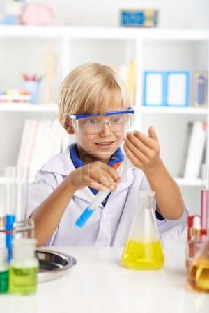 Photo for Schoolboy looking at foam that is coming out of test-tube with reagent - Royalty Free Image
